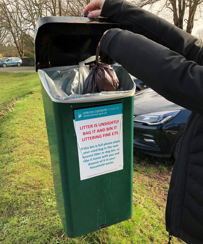 Councillor putting dog-poo bag in bin