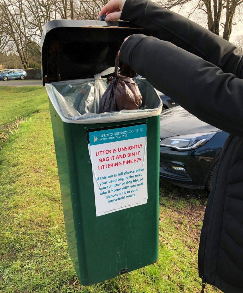 Councillor putting dog-poo bag in bin