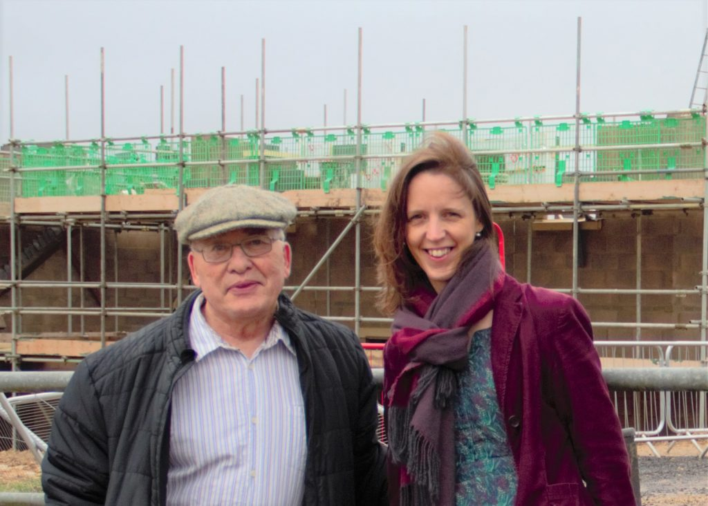 Councillors Norman Kay and Catherine Braun next to a building site.