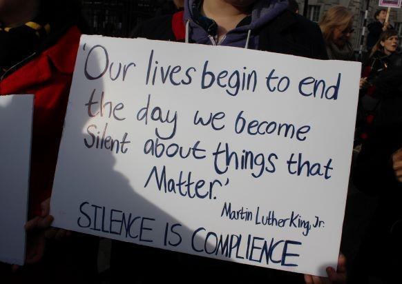 Placard saying 'silence is compliance'